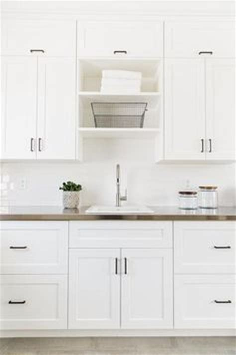 white shaker cabinets with bronze hardware all white laundry room features white shaker cabinets