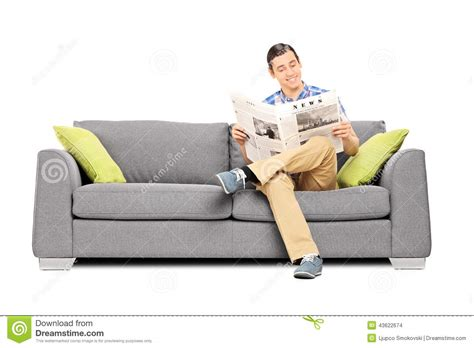 the man on the couch peaceful young man reading the news seated on sofa stock