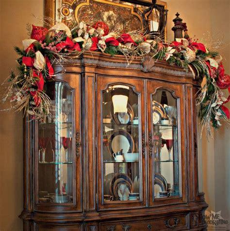 curio cabinet christmas decorating ideas christmas garland over a hutch decorate all around the