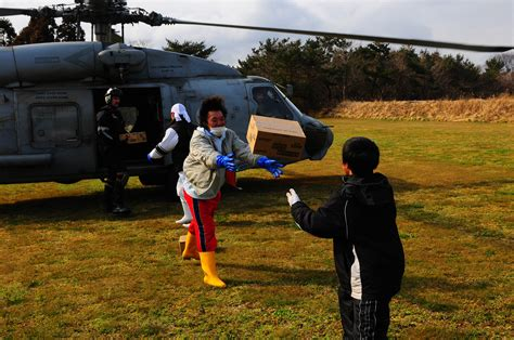 residents help unload humanitarian aid from a black hawk helicopter in file us navy 110322 n uo379 304 japanese citizens unload