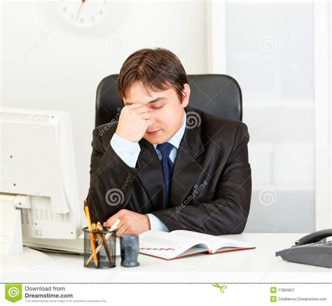 Sitting At Desk by Tired Modern Businessman Sitting At Office Desk Royalty