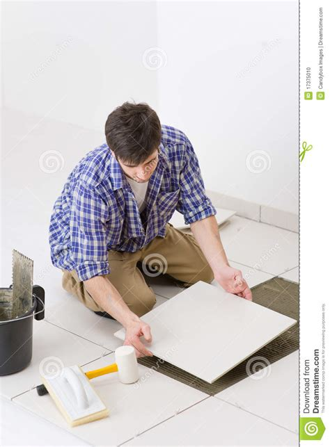 home improvement handyman laying tile stock photo