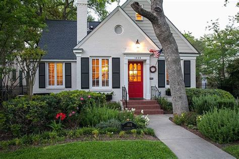 white cottage with shutters and front door via zillow