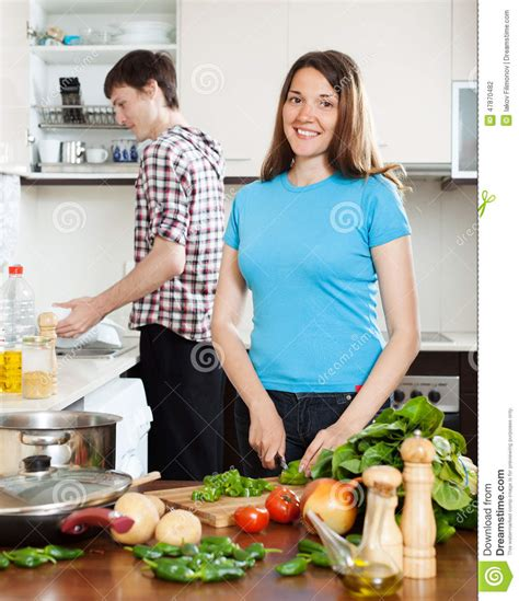 health washing and a kitchen update healthy girl s kitchen woman cooking food while man washing dishes stock photo