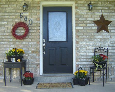front door summer decor idea with flowers and black chair