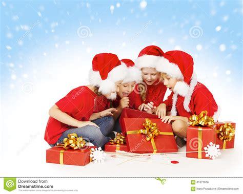 christmas children open presents kids group in santa hat