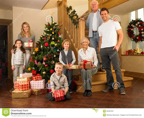 family with gifts around the christmas tree stock image