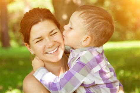 mom images mom and son child kisses his mother on nature background posit stock image image of kissing