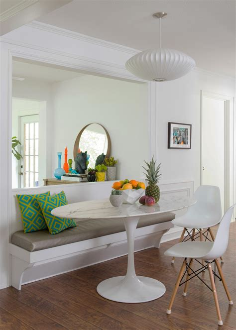 Banquette bench with green cushions and oval dining table plus eames chairs also round wall