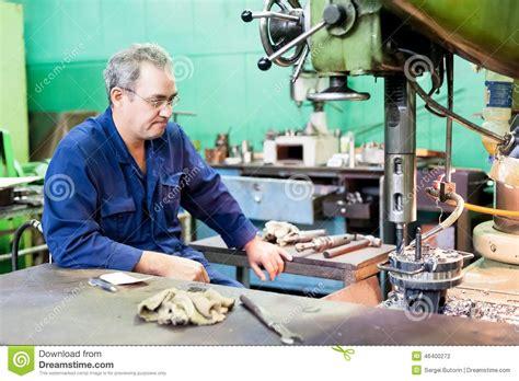 senior milling machine operator works at machine editorial