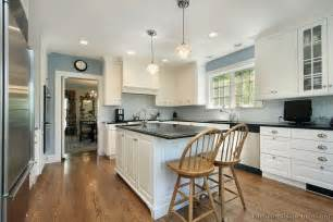 white cabinets blue gray walls black counter white subway tile backsplash yep kitchen