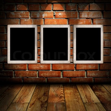 Against A Brick Wall empty frames in a room against a brick wall stock photo