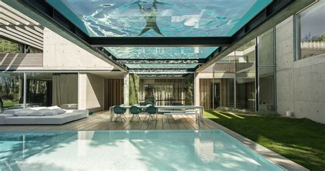 glass wall house elevated glass bottomed pool hovers over a second pool in