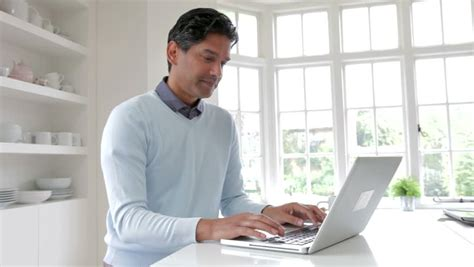asian indian using laptop in kitchen whilst