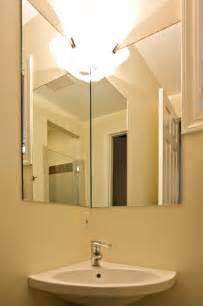 corner sink and corner mirror in small bathroom