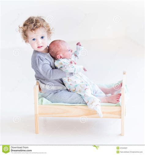 when to put baby in toddler bed toddler girl with newborn baby brother in toy bed stock