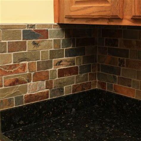 Kitchen with black granite counters and slate backsplash