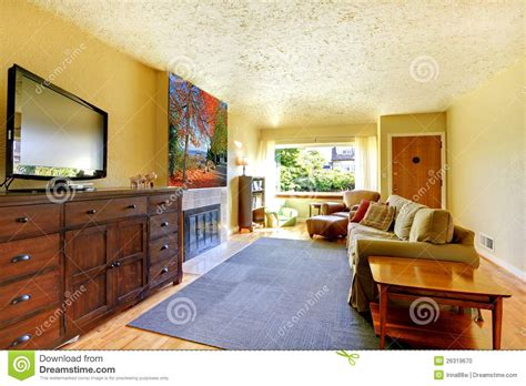 dresser in living room living room with grey rug yellow walls and tv on large