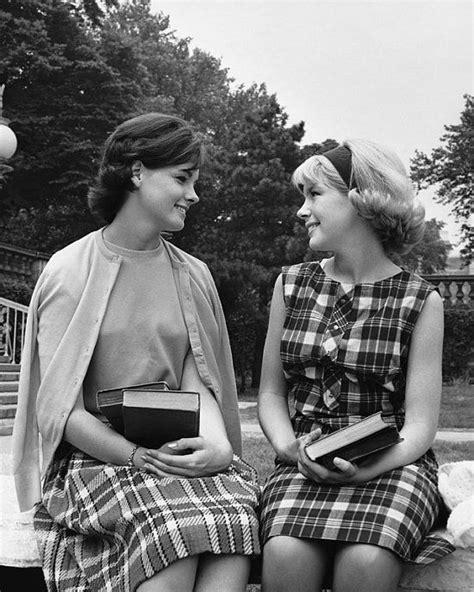 1950s teen fashion for teenage boys schoolgirls having a conversation holding books 1950s