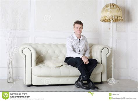 a man and a couch happy man in shirt and pants sits on white leather sofa