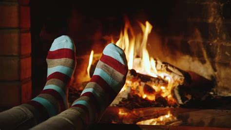 comfort of home the girl warms his feet by the fireplace concept warmth