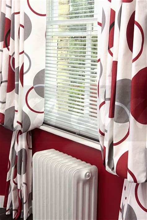 red and white patterned curtains image close up of white slatted blind and red patterned