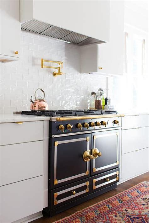 gold  black french stove  white flat front kitchen