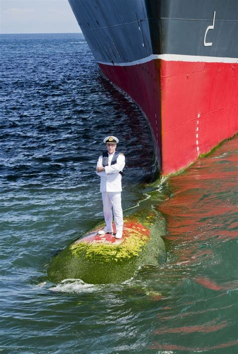 bow of his boat captain poses for epic picture on bow of his huge ship