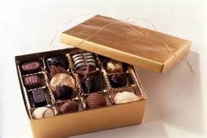 a chocolate box sits open displaying gourmet chocolates