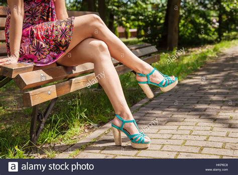 park bench legs young girl in red dress and green shoes sitting on a park