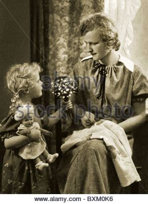 1930s 1940s woman mother with girl daughter kneeling on