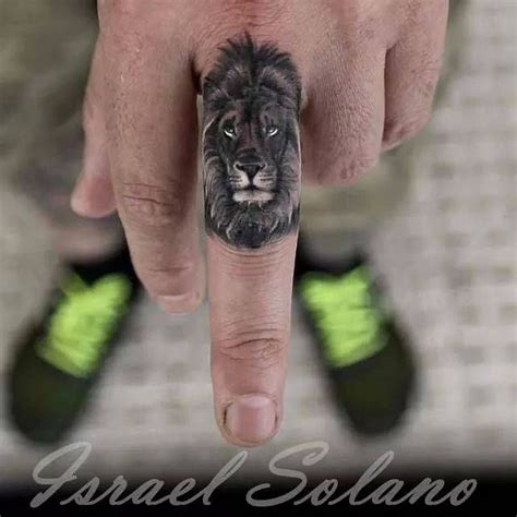 lion tattoo on finger black and grey on the left middle finger