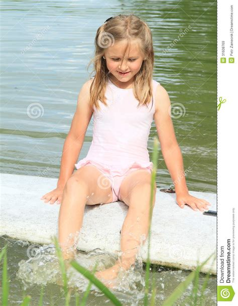 young teen pw smiling little girl sitting on surf board stock image