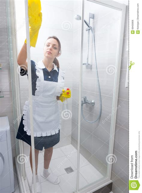 maid in bathroom maid or housekeeper cleaning a shower cubicle stock photo