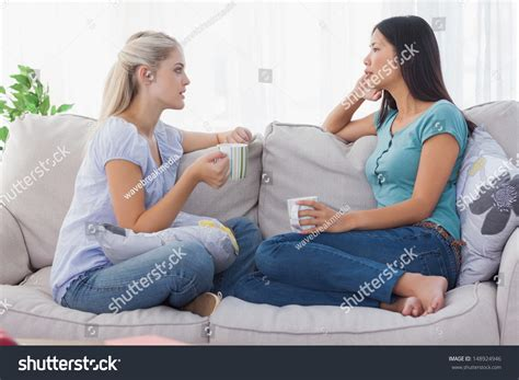 having on couch friends drinking coffee having serious chat stock photo