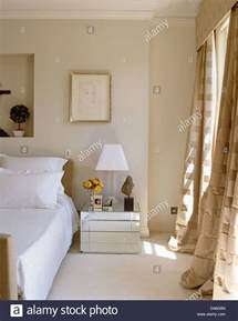 table next to bed white l on mirrored bedside table next to double bed in