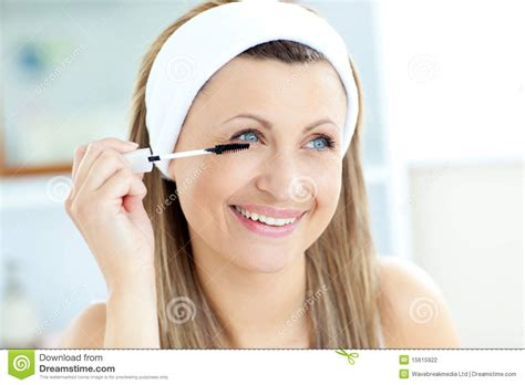 women using the bathroom jolly young woman using mascara in the bathroom stock photography image 15615922