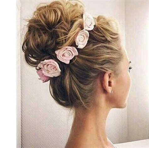 formal hairstyles with flowers voluminous high bun updo made with curls and crowned with