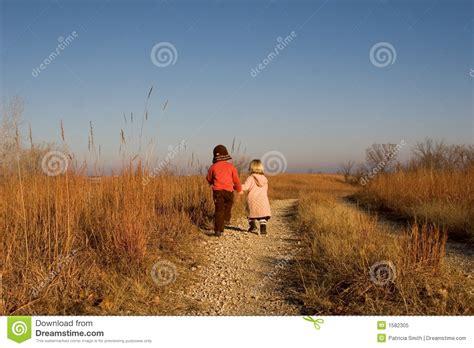 wandlen kinder kinderen die onderaan de weg wandelen stock afbeelding