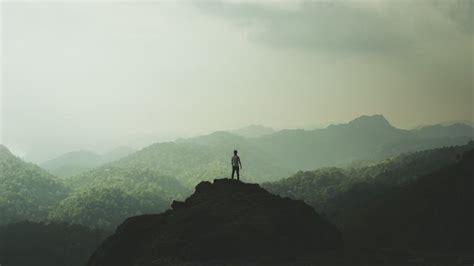 man standing on mountain top free photo man standing on top of a mountain and enjoying