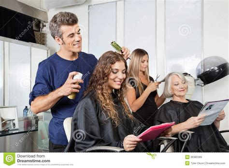 hairdressers setting up client s hair in salon royalty