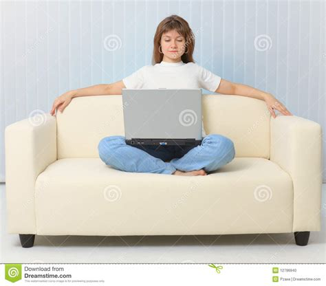 girl sitting on couch beautiful girl sitting on couch with laptop stock photo