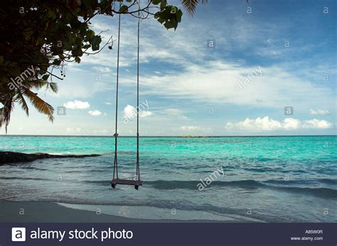 swings over the ocean a beach swing over the shallow water of the sea in the