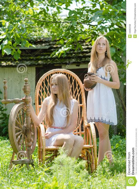 young women  country yard  spinning wheel