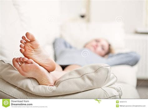 feet on couch young woman lying on sofa focus on her feet stock image