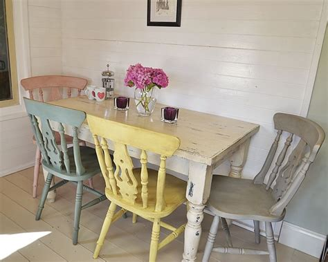 this fabulous dining set has four pastel chairs painted in