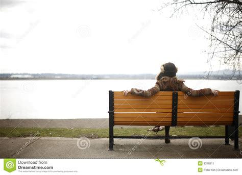 sitting in a park bench woman sitting on park bench stock image image 8316511