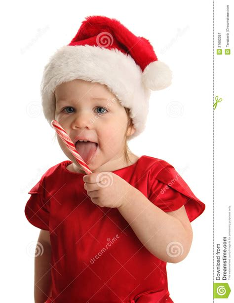 child eating a candy cane wearing a santa hat stock image