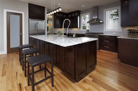 lighter granite with espressor cabinets, lighter flooring