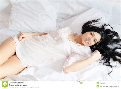 how to look sexier in bed beautiful woman relaxing lying on a white bed in pajamas